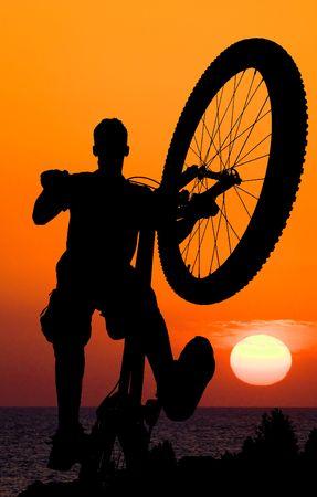 mountain biker silhouette on sea sunset background