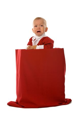 inconsolable: crying little boy in red Santa Claus clothes standing in big box with christmas gifts, isolated on white