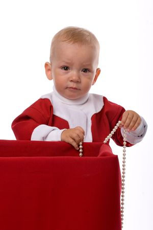 inconsolable: funny little boy in red Santa Claus clothes standing with pearl necklace near big box with christmas gifts, isolated on white Stock Photo