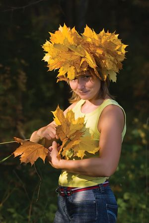 twining: woman in yellow maple wreath twining another one on nature background