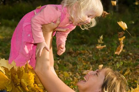 happy smiling woman with laughing little daughter in hands lying on the earth covered by yellow leaves photo