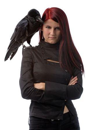 young woman looking like a witch in black clothes with big raven on her shoulder, isolated on white photo