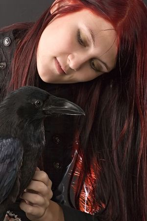young woman with long red hair looking gently at her big black raven photo