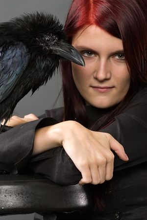 young woman looking like a witch in black clothes with big raven photo