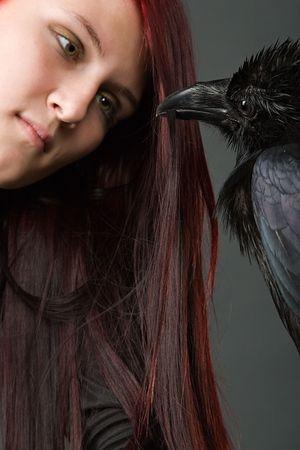 mujer joven con el pelo largo de color rojo mirando a los ojos de negro cuervo grande Foto de archivo - 2005476