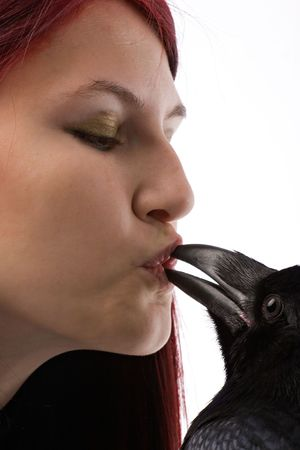 face of young red-haired woman with big black raven putting its beak in her mouth on white background photo