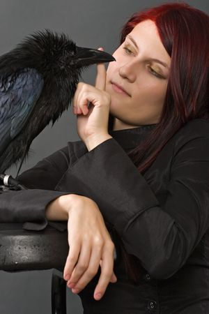 young red-haired woman looking at her big black raven on grey background photo
