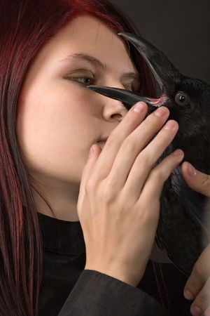 young woman with long red hair and big black raven photo