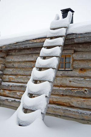 snowy ladder near log cabin in december photo