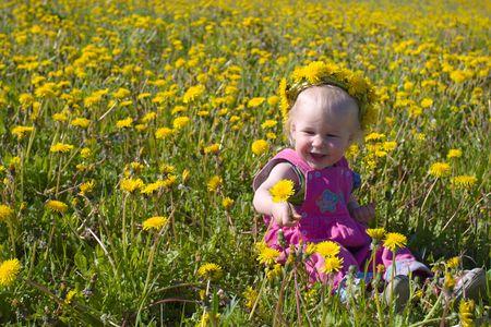 little girl with dandelion diadem on beautiful meadow photo