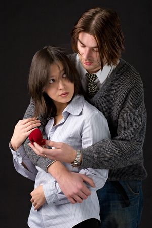 young  couple with box with wedding rings in hands on black background photo