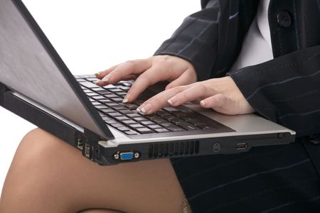 closeup of notebook on womans knees and her printing hands photo