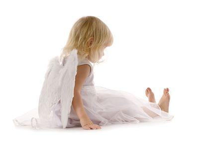 sadly: Purtroppo bambina seduta in abito bianco e ali di angelo sulla schiena isolato su bianco