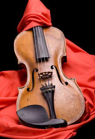 violin on folded scarlet silk on black background photo