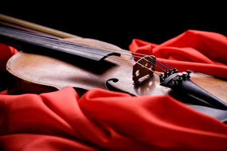 violin: closeup of old violin on folded scarlet silk on black background Stock Photo