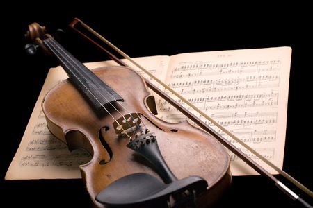 old violin with fiddlestick on music sheet isolated on black background