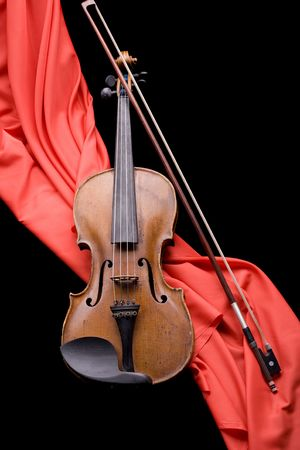 old violin with fiddlestick on folded scarlet silk diagonal on black background photo