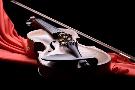 old violin with fiddlestick on folded scarlet silk on black background photo