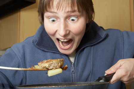 bulging: frightened cooking woman with cutlet and frying pan in hands and bulging eyes Stock Photo