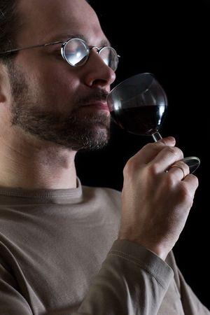 man in glasses tasting red wine on black background photo