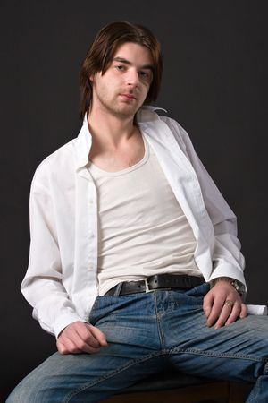 shirt unbuttoned: unshaven relaxed man sitting on chair in unbuttoned white shirt and jeans over black