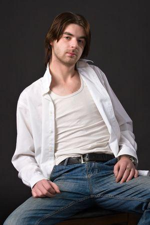 shirt unbuttoned: unshaven rilassato uomo seduto sulla sedia in unbuttoned camicia bianca e jeans sul nero  Archivio Fotografico
