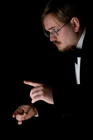 Choir conductor wearing a black tuxedo, photo on black background photo