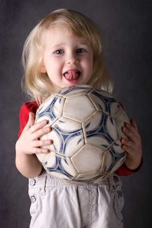 carry out: beautiful blonde small girl with soccer ball over grey