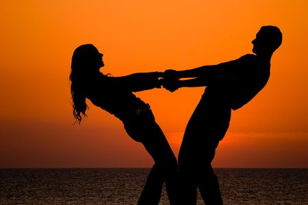 silhouettes of happy young couple holding by hands on orange sea sunset background Stock Photo