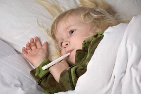 sick child in bed under blanket with thermometer in mouth photo