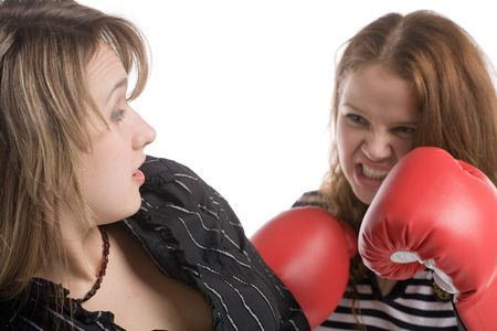beat women: angry woman in boxing gloves going to strike another young woman, isolated on white