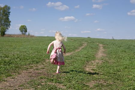 little girl running along the road across green summer meadow photo