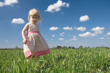 little girl on green spring meadow and blue sky background photo