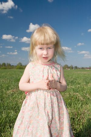 little blonde girl on green meadow and blue sky background photo