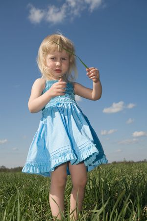 funny little girl with blade of grass in hands on green summer meadow photo