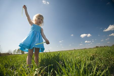funny little girl in blue dress on green meadow and blue sky background photo
