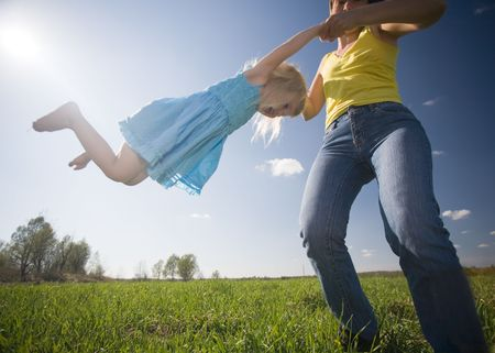 young mother with happy little daughter whirling on green sunny meadow photo
