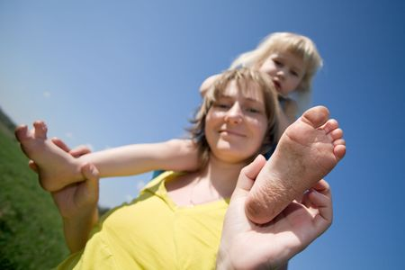 dirty feet: happy mother with little daughter sitting on shoulders over green meadow and blue sky background Stock Photo