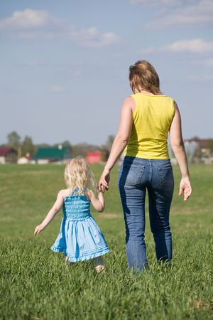 mother walking with her daughter across green summer meadow Stock Photo - 3058438