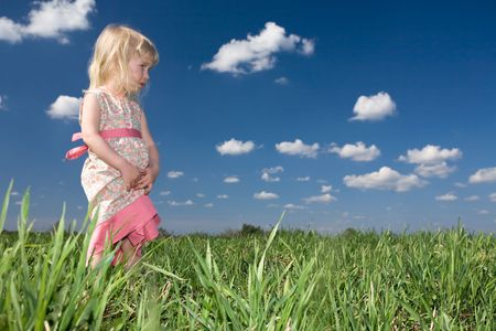toddler girl on green summer meadow and blue sky background photo