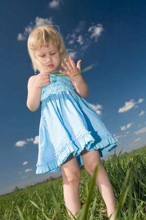 little girl with blade of grass in hands on green summer meadow photo