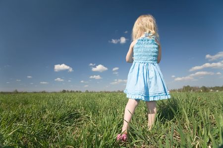 little girl in blue dress standing turned her back on wide green meadow and sky background photo