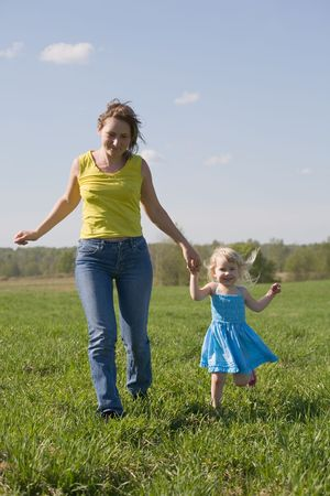 happy mother running with her little daughter across green summer meadow photo