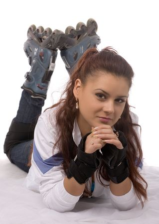 lying young beautiful woman in roller skates on white background photo
