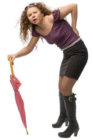 lustige junge Frau Biegen ab Rheuma Schmerzen mit Regenschirm als Krücke isoliert auf weißem