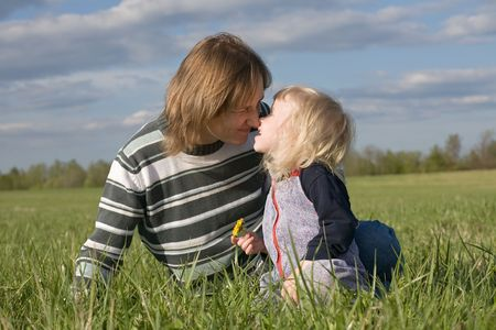 happy mother and little daughter kissing on green summer meadow photo