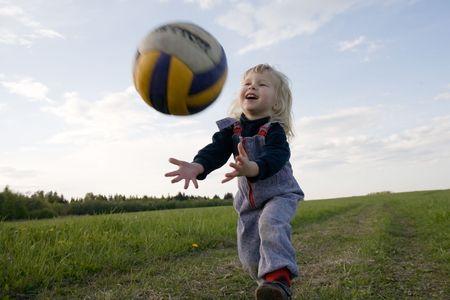 catch: bambina con la palla in mano a sfondo natura  Archivio Fotografico