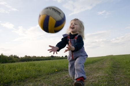 catching: little girl with ball in hands on nature background