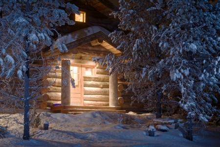 acogedora cabaña de madera en los bosques oscuros de invierno  Foto de archivo
