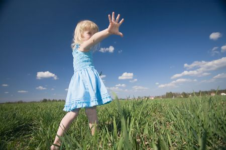 funny little girl in blue dress on green meadow and blue sky background